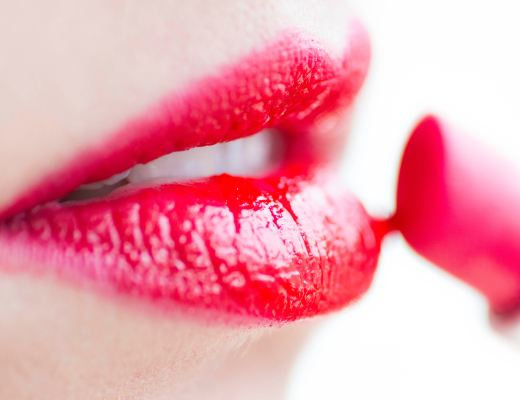 Woman applying red lipstick to lips