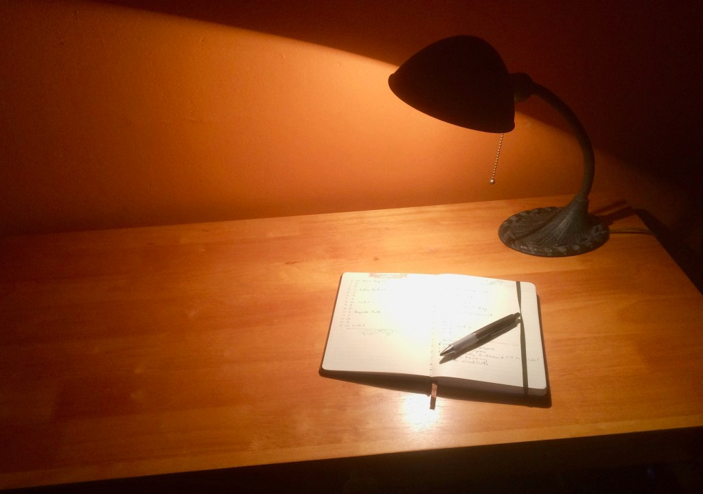 Simple wood desk with open journal and lamp.