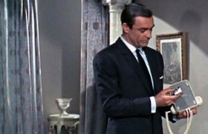 "James Bond checking the telephone for a bug. Of course, he finds one. Image from ""From Russia with Love."""