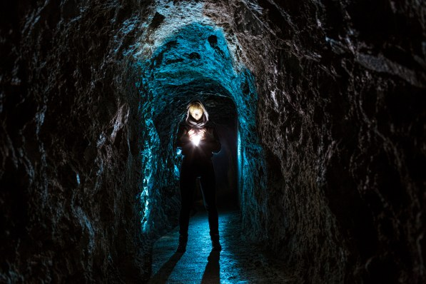 Mysteriously lit female fugure in an underground corridor