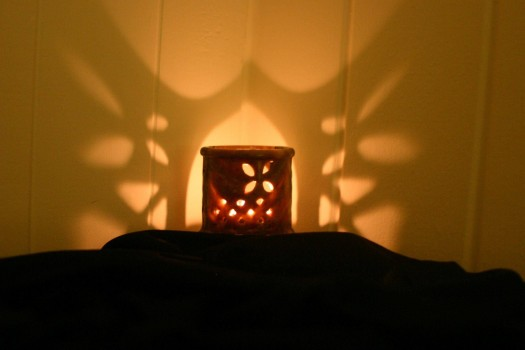 candle casting patterns of light on the wall