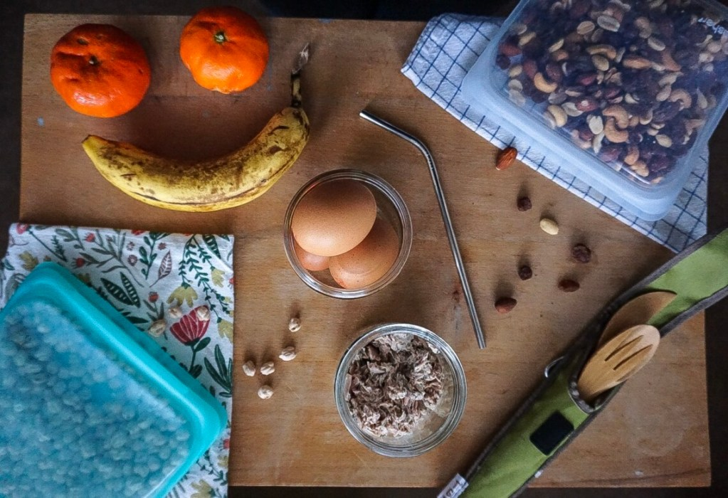 Snack flat-lay, with fruit, chickpeas, hard-boiled eggs, bamboo utensils and 2 Stasher bags