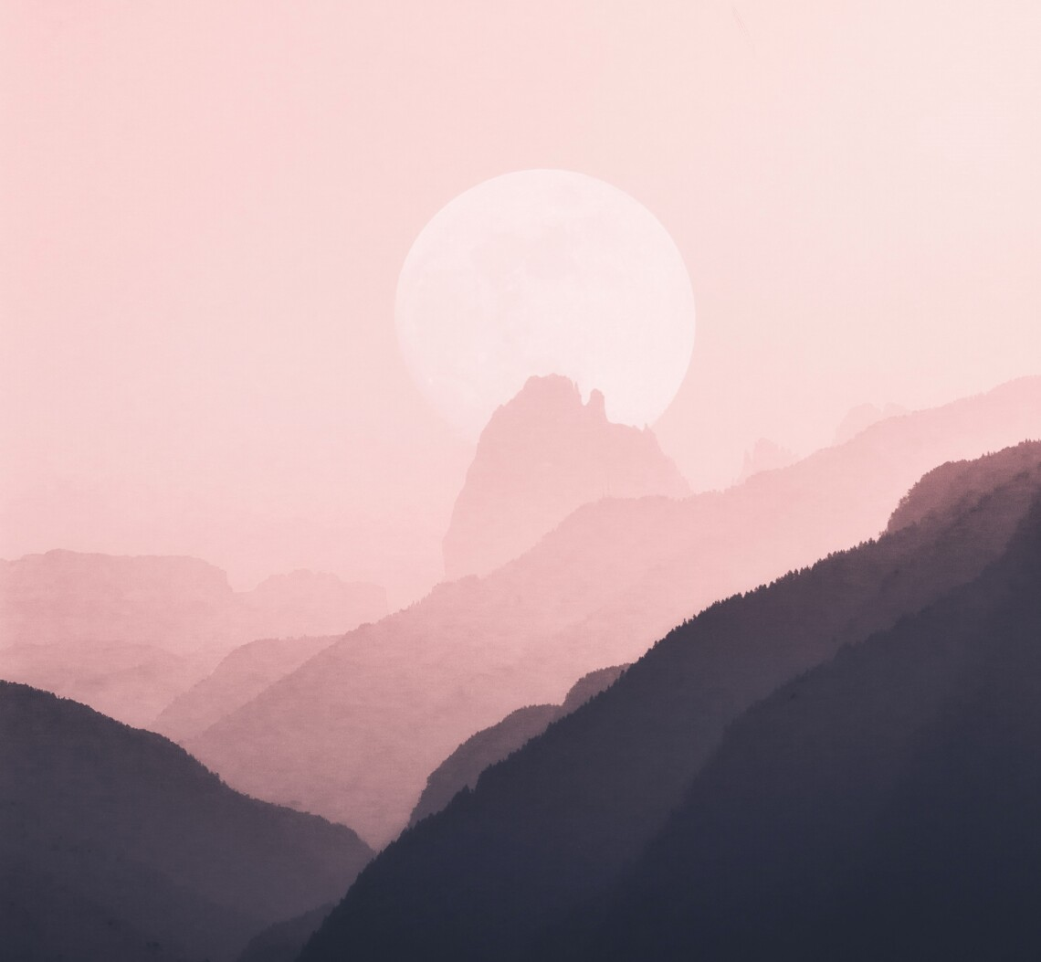 An overly-large full-moon hides behind a mountain in a mountain range. The photo is distorted to appear overly pink and dreamy