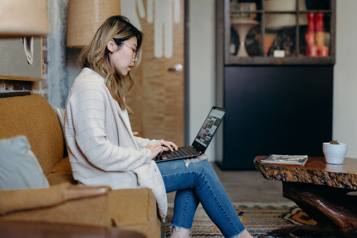 A woman sits on a couch in an apartment on her laptop