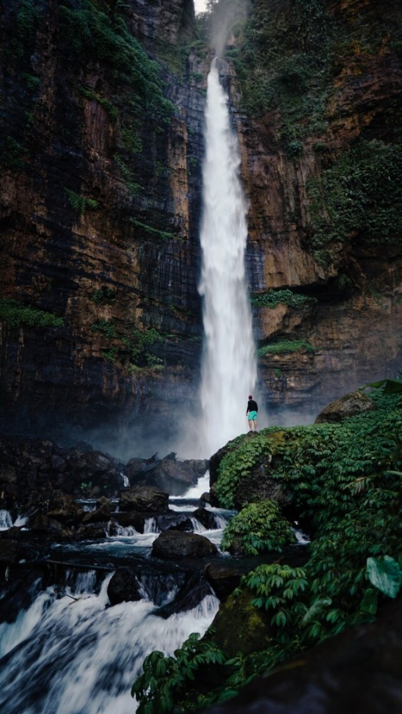 person standing next to a very high waterfall