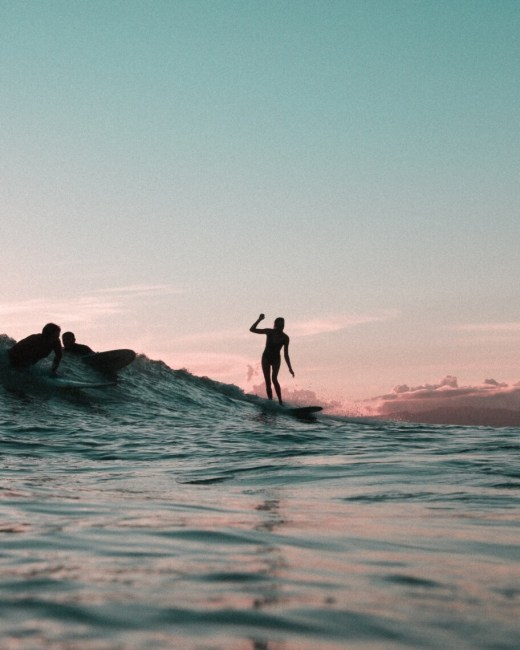 A woman stands atop her surf board, looking like she is dancing on the waves. She is silhouetted and there is a dreamy dark blue and pink sky behind her