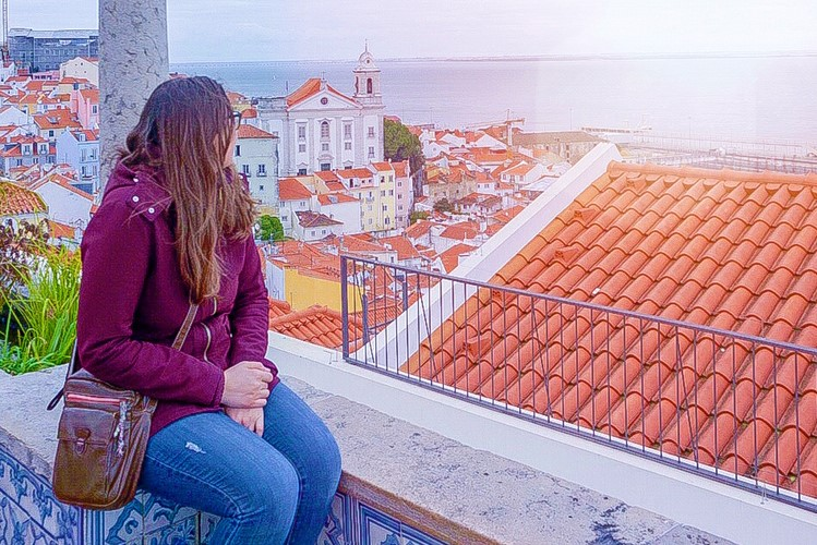 A woman sits with her face away from the camera, looking out at a viewpoint over red tiled rooftops and water