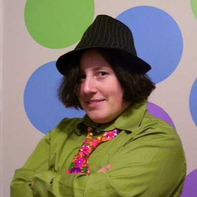 An image of Keffy R.M. Kehrli wearing a Black hat and green shirt standing in front of a wall with colorful circles painted on a light background
