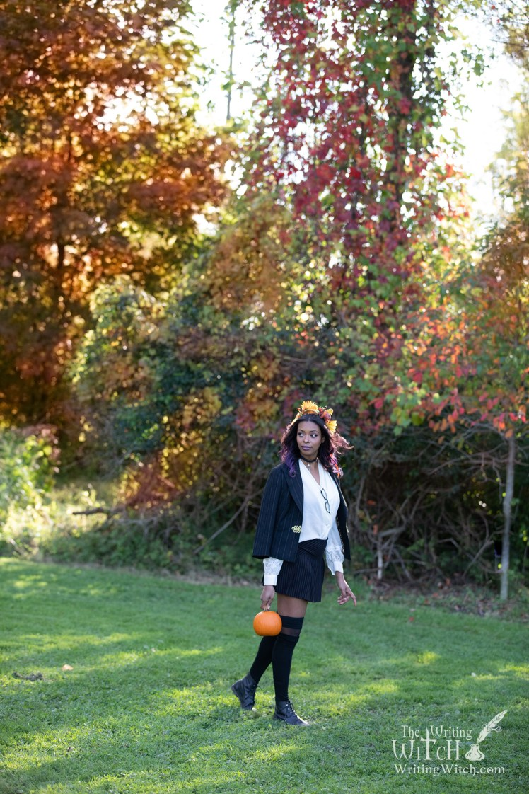 Modern witch outdoors with pumpkin and Autumn leaves.