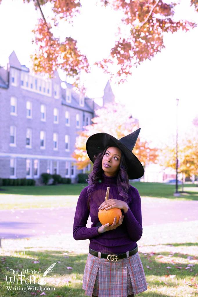 Woman with witch hat and pumpkin.