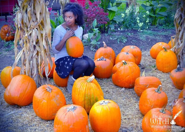 woman holding a pumpkin in a pumpkin patch