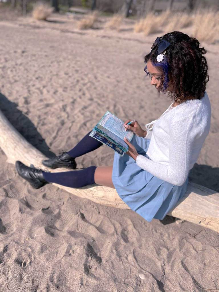 woman writing in a journal on the beach