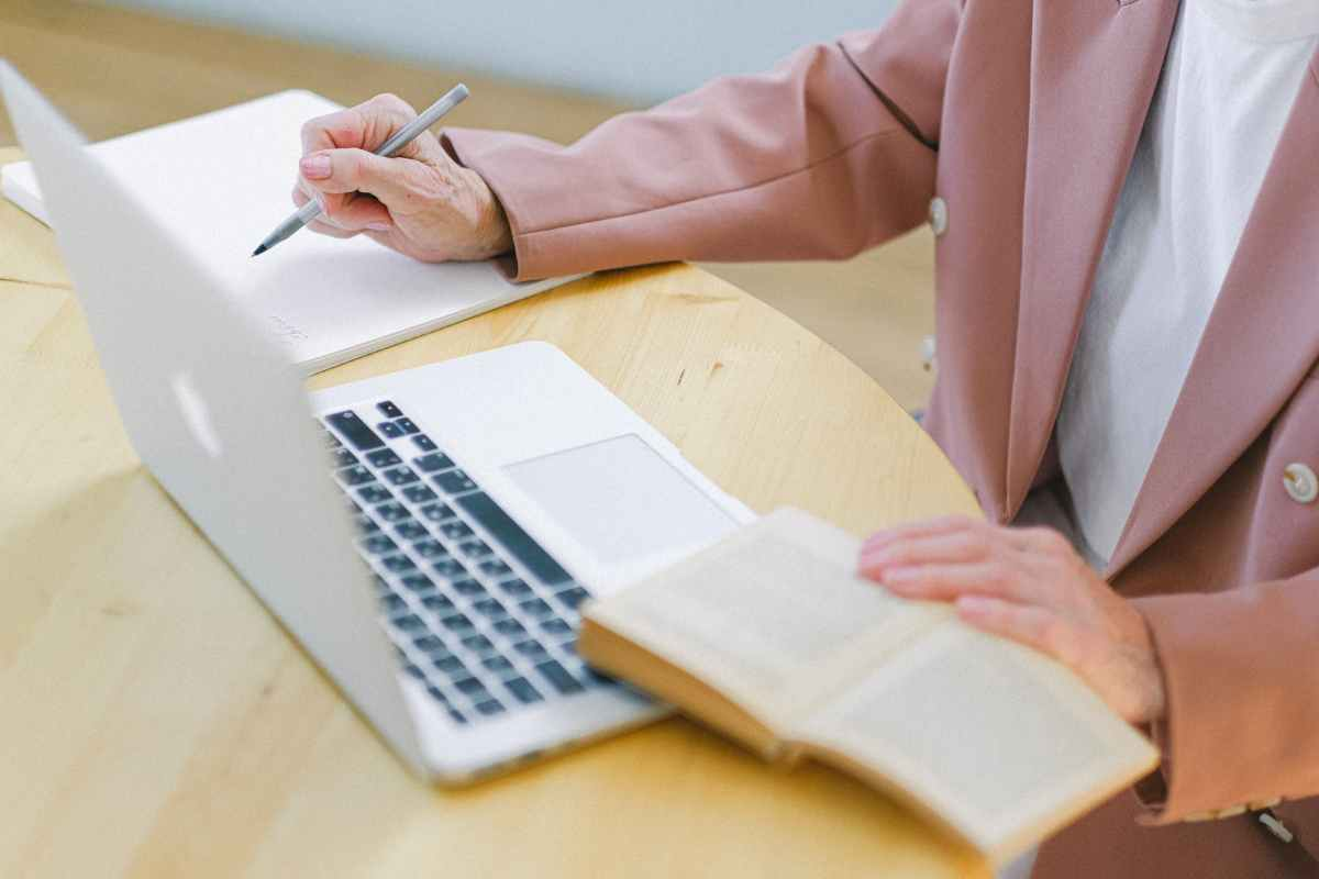 senior woman comparing information in book and in laptop