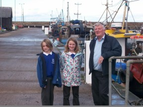 Gilbert Farquhar local retired fisherman with some of P5/6 on a visit to the harbour