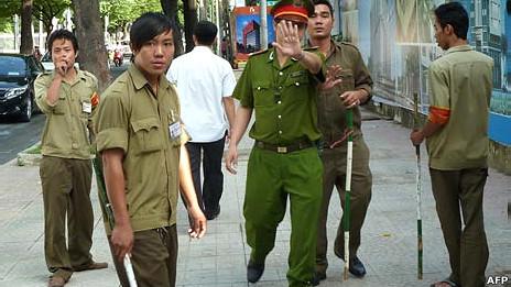 Một cảnh sát giơ tay ngăn phóng viên nước ngoài chụp ảnh tại phiên tòa nhân quyền ở thành phố Hồ Chí Minh hồi tháng Tám với các dân phòng đứng xung quanh