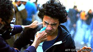 Un manifestante intenta lavar el gas lacrimógeno de los ojos de otro manifestante en Egipto
