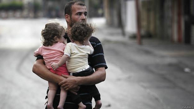 Hombre carga a sus hijos en Gaza