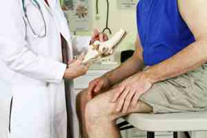 A doctor using a skeletal model of the human knee to explain to her patient the diagnosis of his problem.