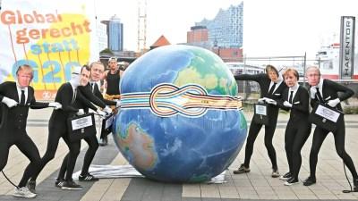 反對全球化的示威者日前在德國漢堡易北愛樂廳前演出行動劇,抗議將在漢堡舉行的G20峰會。p1168-a4-01
