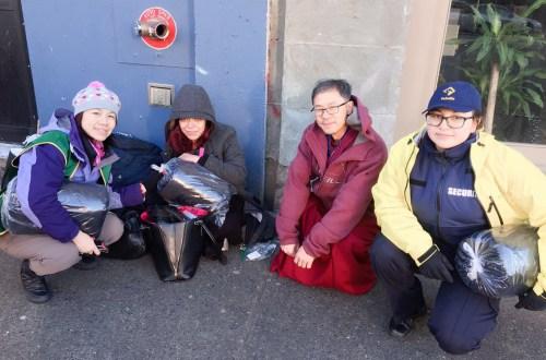 華光義工和社區保安員派發睡袋給遊民