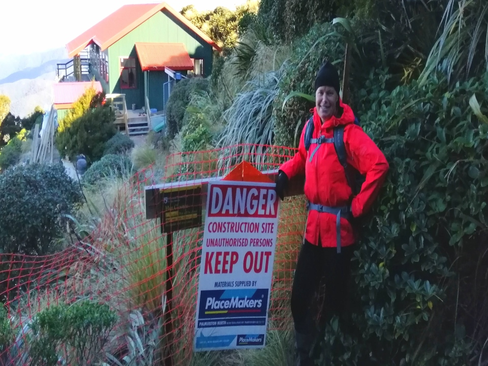 Tramper standing near a construction sign for Powell Hut