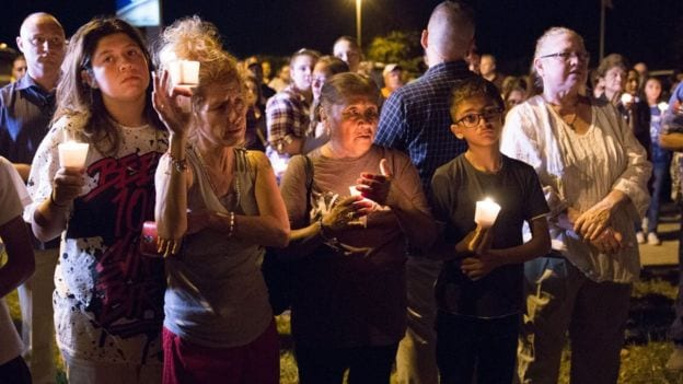 A community of mourners hold vigils at church where 26 people were killed