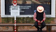 A gondolier checks his mobile phone while waiting for tourists in Venice - As italians try to kickstart the economy