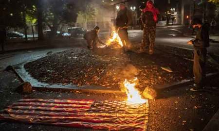 A small group of racial justice protesters watch a burning American Flag as post US election riots erupted