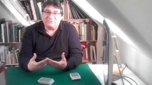 Screenshot aus dem Interview; Roberto sitzt an seinem Tisch, vor ihm auf einer grünen Close up - Matte liegt ein Kartenspiel