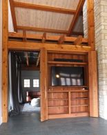 The door to the office is a barn type slider (open, behind TV cabinet), while the doors on the TV cabinet open accordion style to take up less floor space.