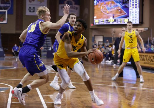 SIOUX FALLS, SD - NOVEMBER 25: Taz Sherman #12 of the West Virginia Mountaineers drives on Charlie Easley #30 of the South Dakota State Jackrabbits during the Bad Boy Mowers Crossover Classic at the Sanford Pentagon in Sioux Falls, SD. (Photo by Richard Carlson/Inertia)