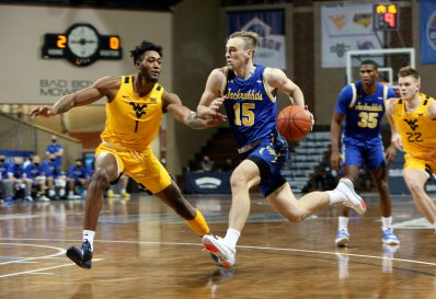 SIOUX FALLS, SD - NOVEMBER 25: Noah Freidel #15 of the South Dakota State Jackrabbits drives to the basket past Derek Culver #1 of the West Virginia Mountaineers during the Bad Boy Mowers Crossover Classic at the Sanford Pentagon in Sioux Falls, SD. (Photo by Dave Eggen/Inertia)
