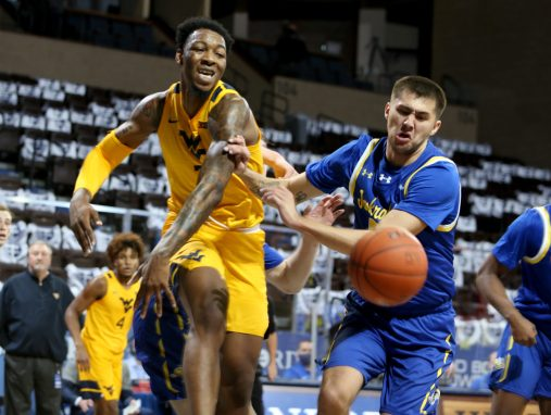 SIOUX FALLS, SD - NOVEMBER 25: Gabe Osabuohien #3 of the West Virginia Mountaineers battles for the loose ball with David Wingett #50 of the South Dakota State Jackrabbits during the Bad Boy Mowers Crossover Classic at the Sanford Pentagon in Sioux Falls, SD. (Photo by Dave Eggen/Inertia)