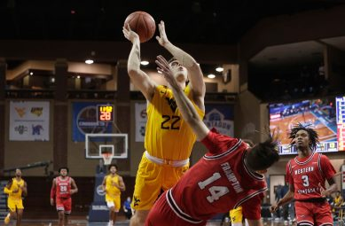 SIOUX FALLS, SD - NOVEMBER 27: Sean McNeil #22 of the West Virginia Mountaineers runs into Luke Frampton #14 of the Western Kentucky Hilltoppers during the Bad Boy Mowers Crossover Classic at the Sanford Pentagon in Sioux Falls, SD. (Photo by Richard Carlson/Inertia)