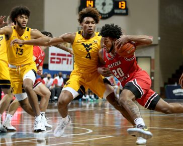 SIOUX FALLS, SD - NOVEMBER 27: Josh Anderson #4 of the Western Kentucky Hilltoppers drives against Miles McBride #4 of the West Virginia Mountaineers during the Bad Boy Mowers Crossover Classic at the Sanford Pentagon in Sioux Falls, SD. (Photo by Dave Eggen/Inertia)