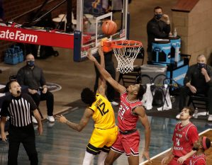 SIOUX FALLS, SD - NOVEMBER 27: Charles Bassey #23 of the Western Kentucky Hilltoppers tries to block Taz Sherman #12 of the West Virginia Mountaineers during the Bad Boy Mowers Crossover Classic at the Sanford Pentagon in Sioux Falls, SD. (Photo by Richard Carlson/Inertia)