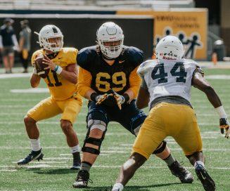 Offensive lineman Blaine Scott (middle) protects quarterback Garrett Green (left) from bandit Lanell Carr. WVU Athletics
