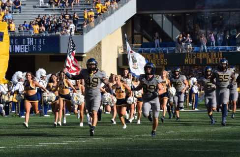 Mountaineers enter Milan Puskar Stadium carrying in a U.S. and West Virginia flag.