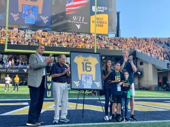 Former WVU quarterback, Chris Gray, was honored by WVU Athletic Director Shane Lyons, from left, former head coach Don Nehlen and his brother and family. Gray died at age 32 in one of the World Trade Centers on 9/11.