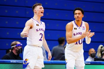 Kansas guard Christian Braun (2) and Kansas forward Jalen Wilson (10) celebrate a three from Kansas guard Marcus Garrett (0) while waiting to check into the game during the second half, Tuesday, Dec. 22, 2020 at Allen Fieldhouse.