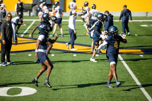 Two cornerbacks warm up during a WVU Football practice on March 27, 2021 in Milan Puskar Stadium. (Duncan Slade/WVSportsNow)