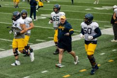 Assistant head coach Matt Moore jogs with several players during a practice in Milan Puskar Stadium on Saturday April 17, 2021. Duncan Slade/WVSN