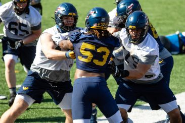 Offensive linemen Doug Nester (left) and John Huges blocking defensive end Eddie Watkins (center) during a WVU Football practice on March 27, 2021 in Milan Puskar Stadium. (Duncan Slade/WVSportsNow)