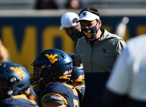 West Virginia Mountaineers head coach Neal Brown talks with his team during warmup Saturday, Oct. 16, 2020, in Morgantown.