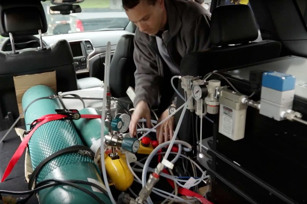 small resolution of marc besch installs emissions testing equipment in a vehicle at the wvu cafee lab
