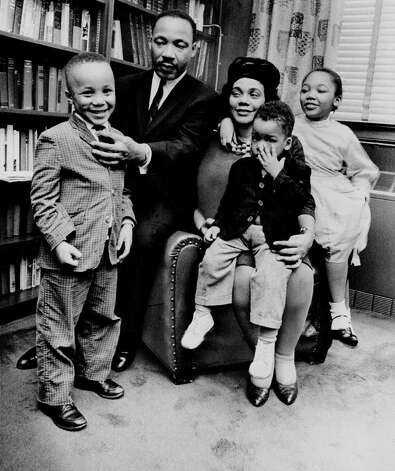 Dr. Martin Luther King Jr. and his wife, Coretta Scott King, sit with three of their four children in their Atlanta, Ga, home, on March 17, 1963. From left are: Martin Luther King III, 5, Dexter Scott, 2, and Yolanda Denise, 7. (AP Photo) / Beaumont