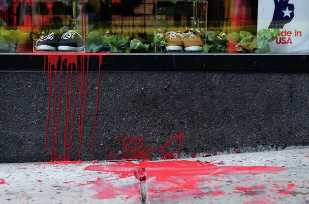 Dried red paint, left by protesters, falls down the side of the American Apparel storefront at 6th Ave. and Pike St. in Seattle on Tuesday, May 1, 2012. A small group of protesters dressed in black grew violent in the early afternoon, using flagpoles, rocks and paint bombs to damage local businesses downtown. Photo: LINDSEY WASSON / SEATTLEPI.COM