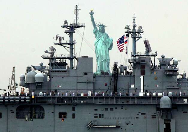 Sailors line the deck of the USS Wasp as she sails by the Statue Of Liberty, in New York, to participate in Fleet Week activities Wednesday. (AP Photo/Richard Drew) Photo: Associated Press / SL