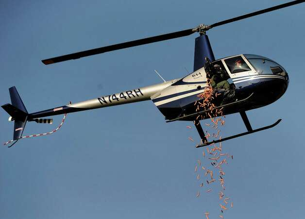 A Helicopter drops nearly 1,000 hot dogs to celebrate American Coney Island's 95th Anniversary at H.Y.P.E Recreation Center field on Wednesday in Dearborn Heights, Mich. Contestants will have 95 seconds to gather as many as they can. The dogs will then be donated to a local dog rescue charity for food. (AP Photo/Detroit News, David Coates) Photo: Associated Press / SL