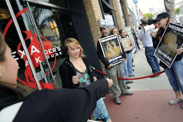 Customer Sarah Jones of San Francisco takes a flier from a protester in front of Alexander's Steakhouse.  Alexander's Steakhouse held their last farewell to foie gras dinner and fundraiser in San Francisco, CA Saturday June 30th, 2012. Photo: Michael Short, Special To The Chronicle